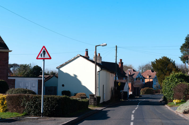 Road amidst buildings against clear blue sky