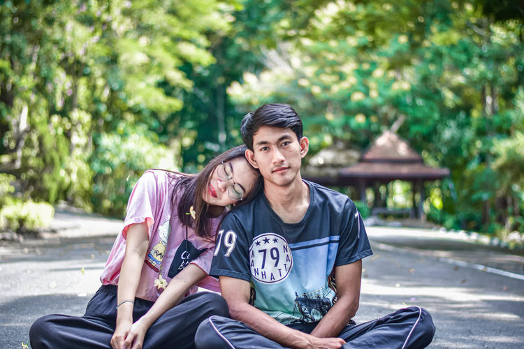 Woman sitting with male friend with eyes closed on footpath