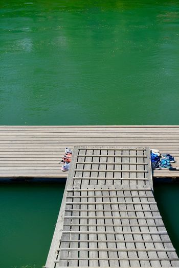 High angle view of man sitting on pier over sea