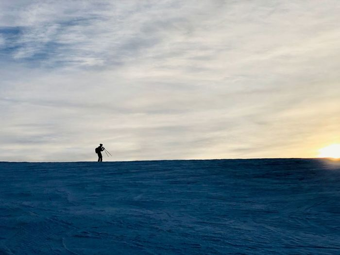 Minimalistic view of hiker walking on snow at sunset Frozen Alone Travel Wanderlust Hiking Hiker Day Nature Sunrays Dusk Sunset Minimalism Minimal Mountain Mountain Range Snow Winter Sky Cloud - Sky Scenics - Nature Real People Horizon Silhouette Outdoors One Person Lifestyles Leisure Activity Standing Sport Full Length