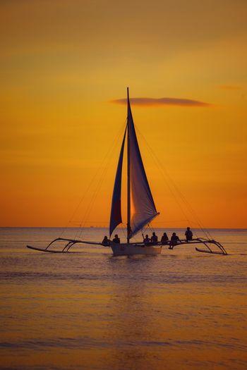Sailboat sailing in sea against orange sky