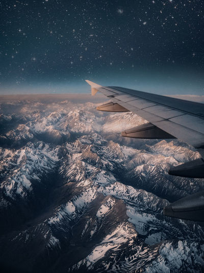 Aerial view of snowcapped mountains against star field at night