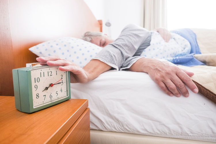 Senior Woman Stopping Alarm Clock While Sleeping On Bed At Home