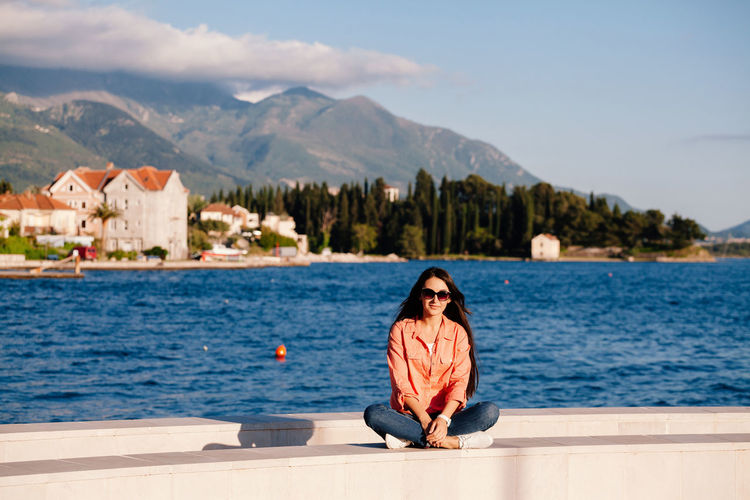 Woman in sunglasses sitting at lake against mountains