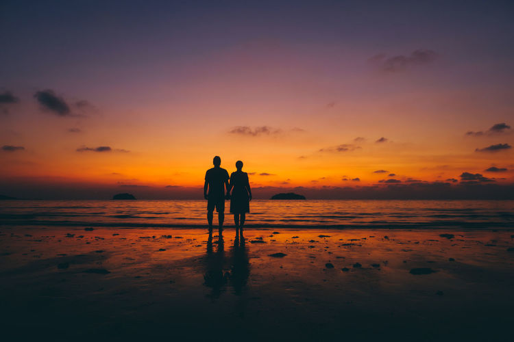 Silhouette couple standing on sea shore at beach against sky during sunset