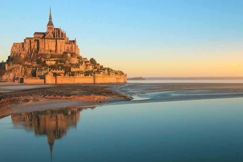 Morning light on Mont Saint Michel and it's reflection in Normandy-France Landscape_photography Landmark Abbey Church Morning Light Normandy France Mont Saint-Michel Water Sky Sea Clear Sky Beauty In Nature Scenics - Nature Nature Sunset Architecture Tranquility Tourism Copy Space Horizon Over Water Land