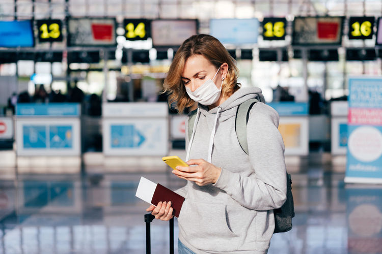 Woman using smart phone while standing with passport and ticket at airport