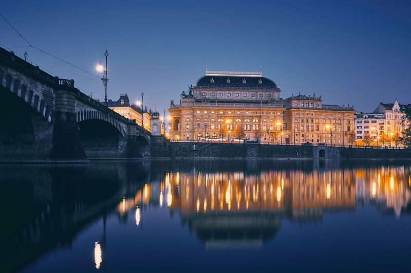 City reflection in vltava river. embankment with national theater at twilight in prague.