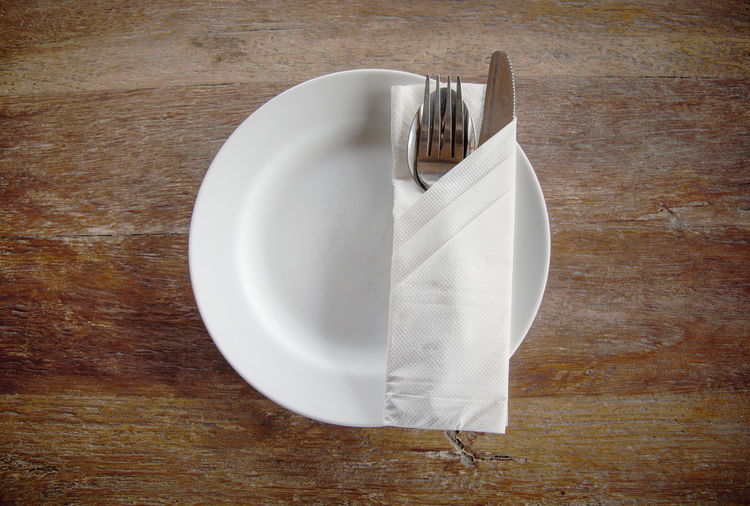 Top view of white circle plate with spoon, fork, knife and napkin on wooden table Fork Knife Spoon Tissue Wooden Table Food And Drink Household Equipment Kitchen Utensil Napkin Plate Resturant Top View White White Color Wood - Material