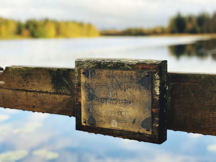 Close-up of old wooden post by lake against sky