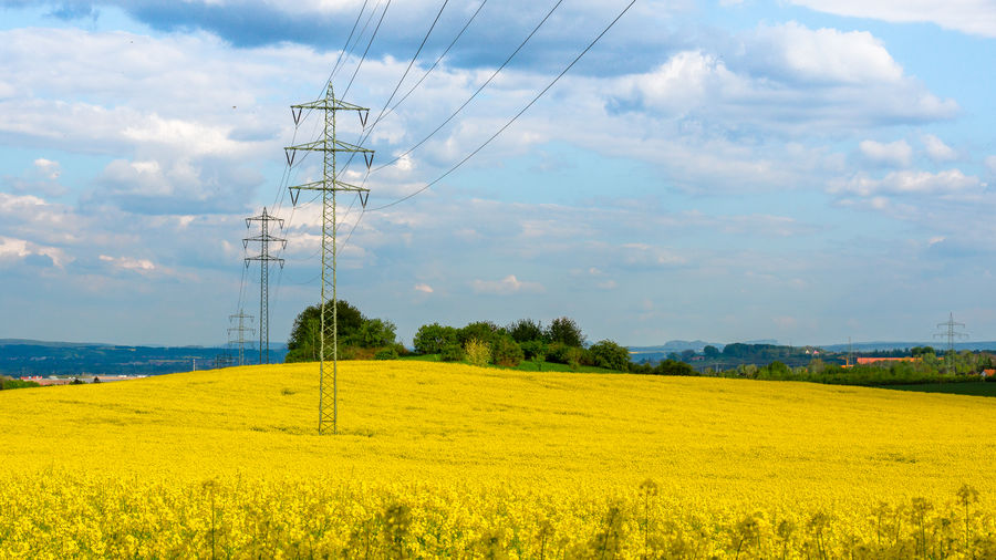 Low angle view of electricity pylons in yellow farm against cloudy sky