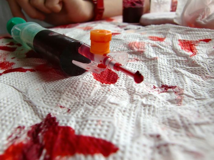 Close-up of artificial blood in syringe on tissue paper