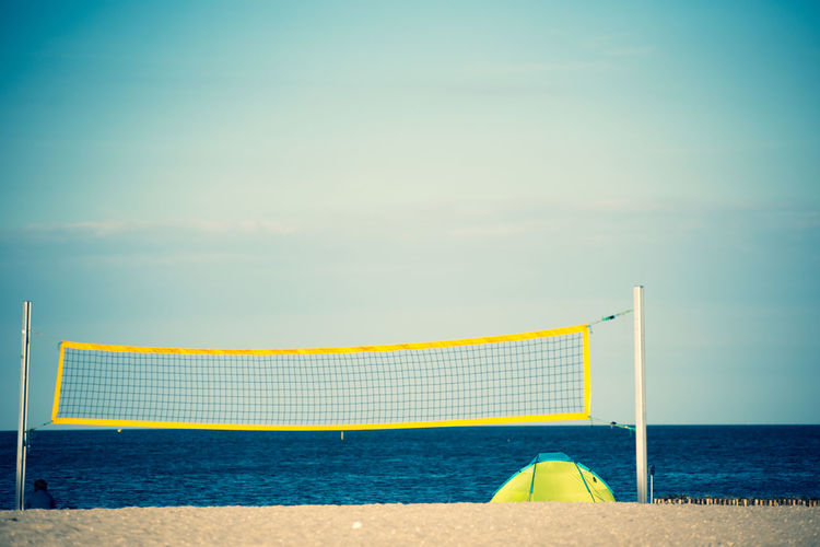 Scenic view of beach and volleyball net against sky