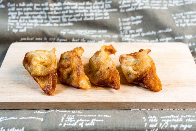 Close-up of fried dumplings on cutting board