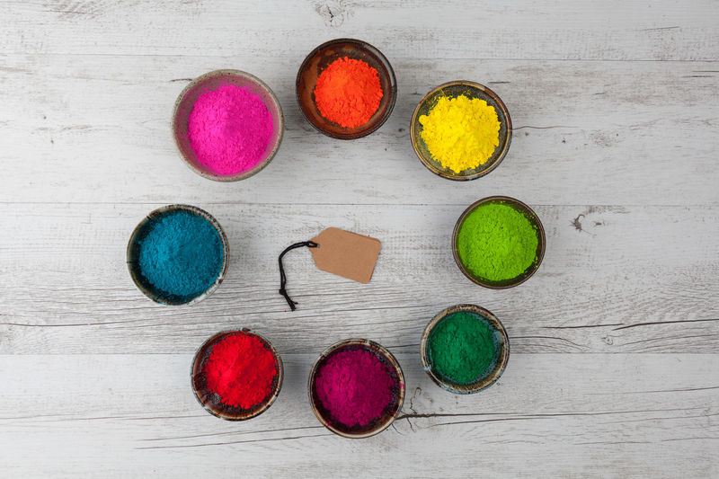 Directly above view of blank label amidst colorful powder paint in bowls on wooden table