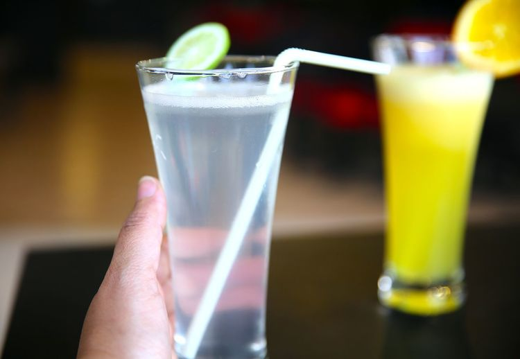 Cropped image of hand holding lemonade at restaurant
