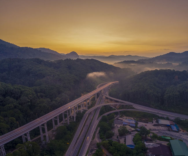 High angle view of bridge over mountains against sky during sunset