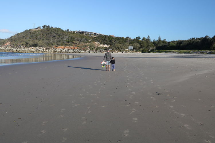Rear view of father and son walking on beach against clear sky