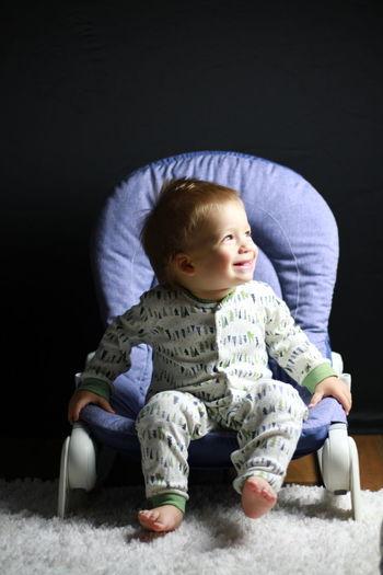 Cute baby boy sitting on sofa