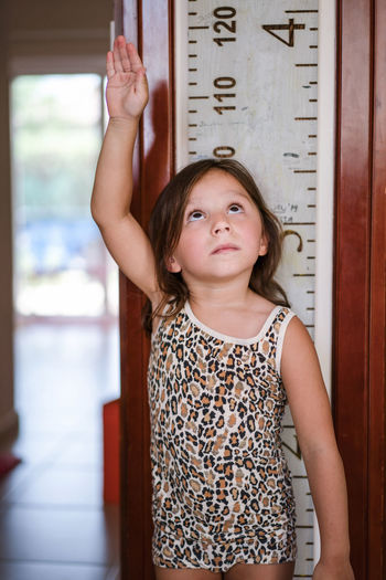 Portrait of a girl standing against wall measuring her height