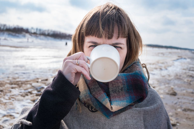 Beach Childhood Close-up Coffee - Drink Coffee Cup Day Drink Drinking Focus On Foreground Food And Drink Headshot Holding Leisure Activity Lifestyles Nature One Person Outdoors People Portrait Real People Sky Warm Clothing Water Young Adult Young Women