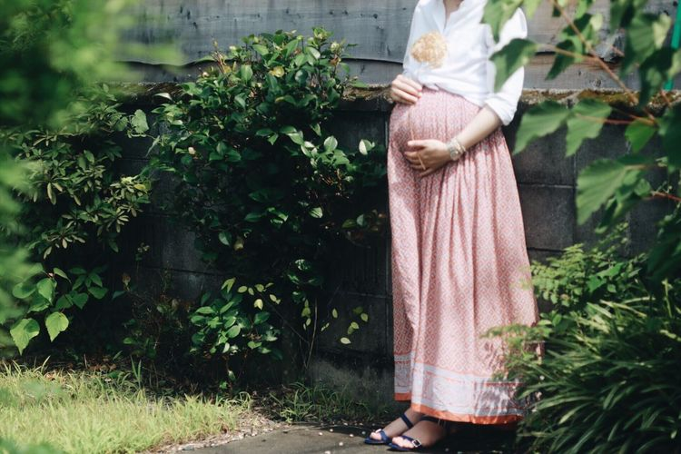 Low section of pregnant woman standing by surrounding wall in yard