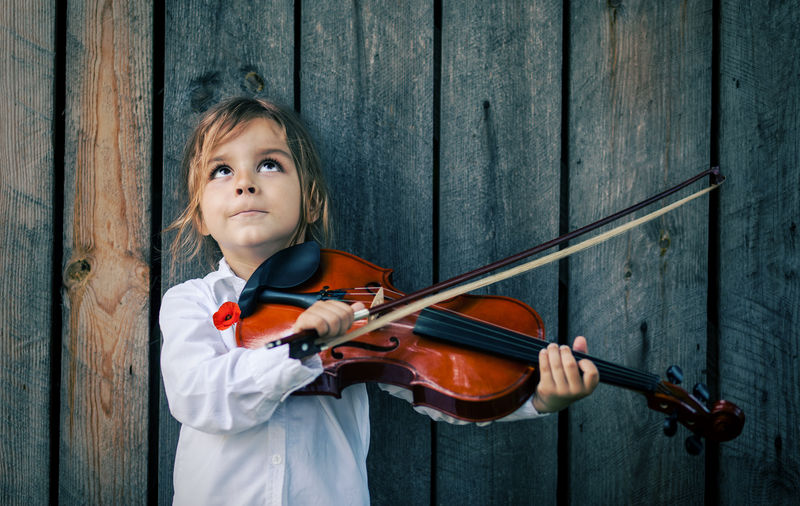 Boy Looking Up While Playing Violin Against Wooden Wall