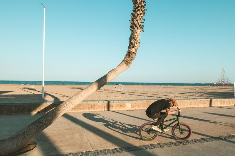 Man riding bicycle on beach against clear sky