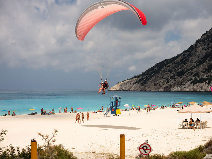 Adventure Beach Beauty In Nature Extreme Sports Flying Horizon Over Water Land Leisure Activity Lifestyles Nature Outdoors Parachute Paragliding Real People Sand Sea Sky Sport Unrecognizable Person Water