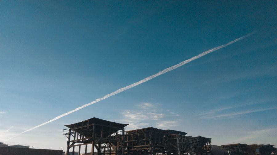 Low angle view of vapor trails in building against sky