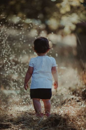 Rear view of baby girl walking on land