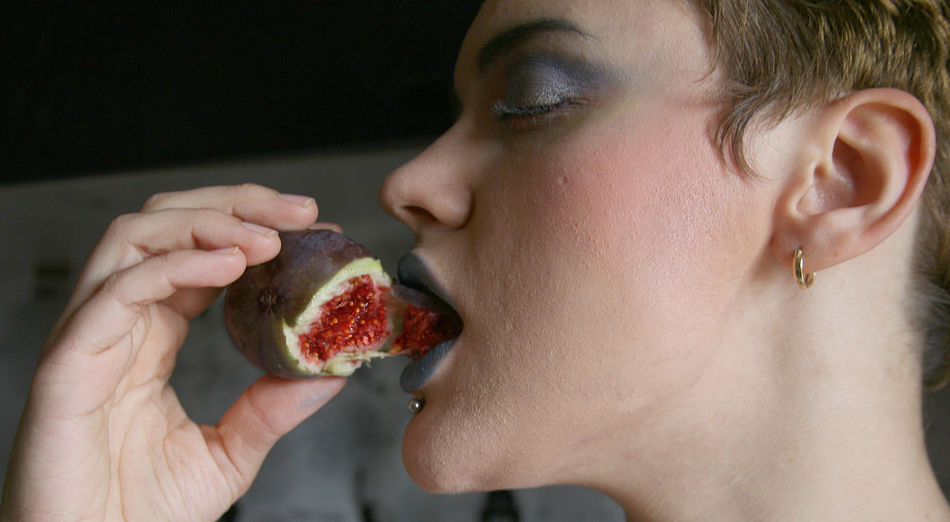 Close-Up Of Young Woman Eating Fig