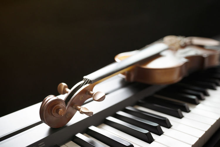 Piano keyboard with violin,top view Music Musical Instrument Musical Equipment Arts Culture And Entertainment Piano Piano Key Black Background Studio Shot Indoors  Wood - Material Close-up No People Classical Music String Instrument White Color Playing Black Color Keyboard Keyboard Instrument String Grand Piano