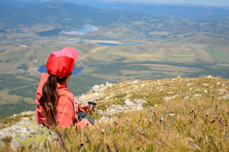 woman with a Cup of coffee in the mountains Freedom Hiking Lifestyle Relaxing Travel Activity Adult Adventure Beauty In Nature Day Drink Enjoying Life Environment Landscape Leisure Activity Looking At View Mountain Mountain Range Nature One Person Outdoors Remote Scenics - Nature Tourism Women