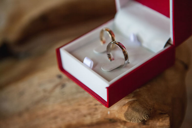 Close-Up Of Wedding Rings On Wooden Table