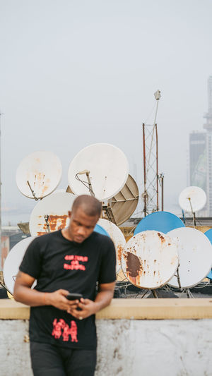 Full length of man using mobile phone against sky