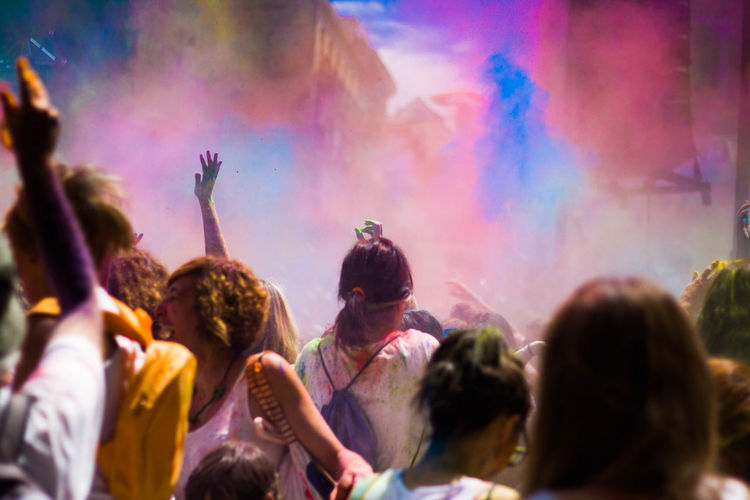 Crowd with arms raised playing holi