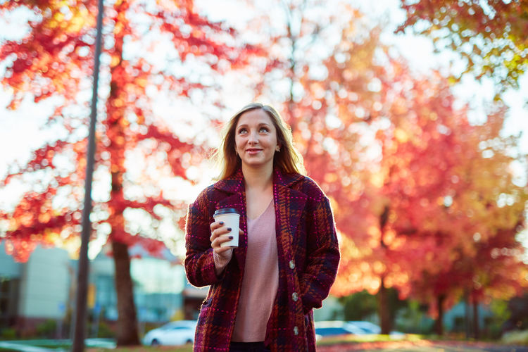 Autumn Beautiful Woman Casual Clothing Coffee - Drink Coffee Cup Day Drinking Focus On Foreground Front View Holding Leaf Leisure Activity Lifestyles Looking At Camera Nature One Person Outdoors Park - Man Made Space Portrait Real People Smiling Standing Tree Young Adult Young Women