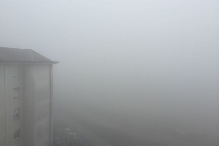Scenic view of foggy weather against sky during winter