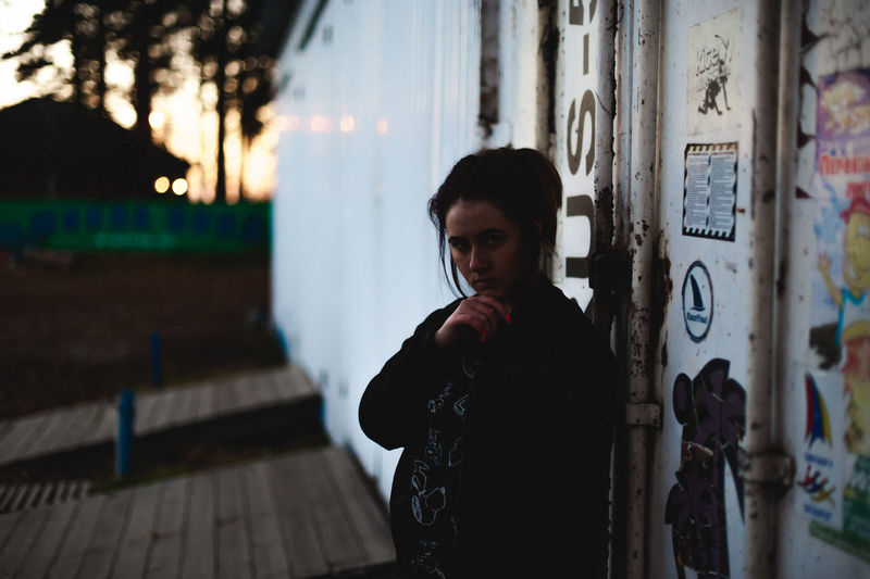 Portrait Of Young Woman With Hand On Chin Standing By Cargo Container