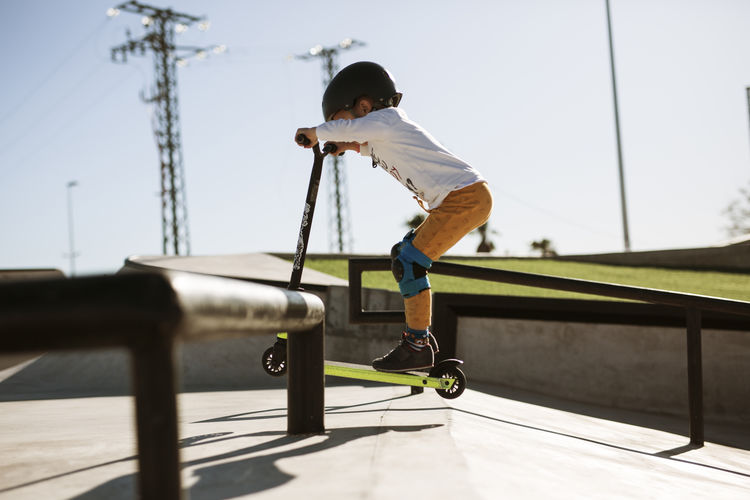 Rear view of boy climbing on umbrella