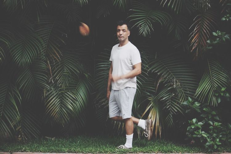 Full length portrait of man standing against palm trees