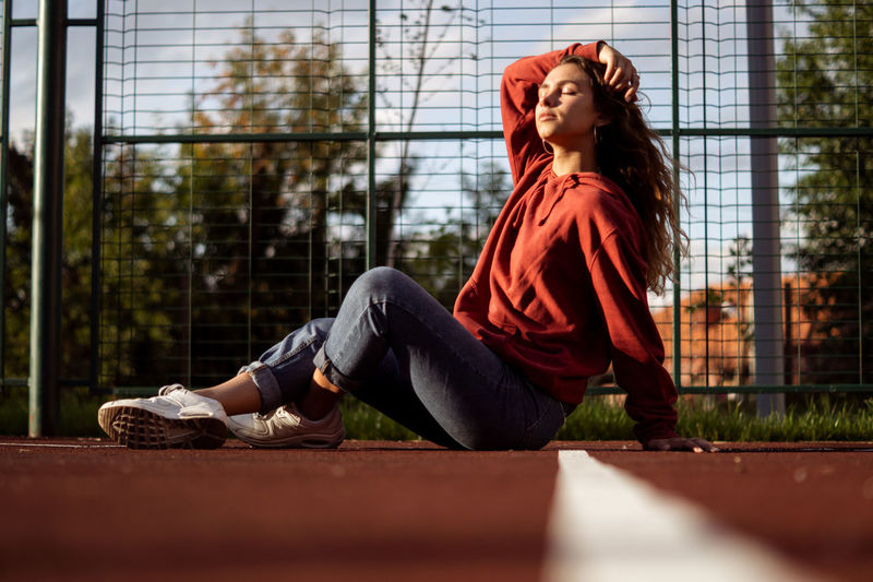 Side view of young woman with eyes closed sitting on sports track