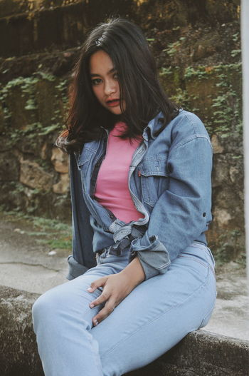 Portrait of young woman wearing denim jacket while sitting on retaining wall