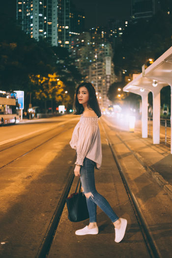 Young woman standing on footpath at night