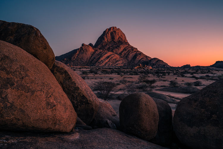 Scenic view of rock formations against clear sky during sunset