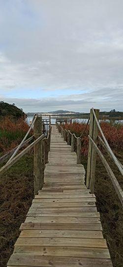 Wooden walkway leading towards sea against sky