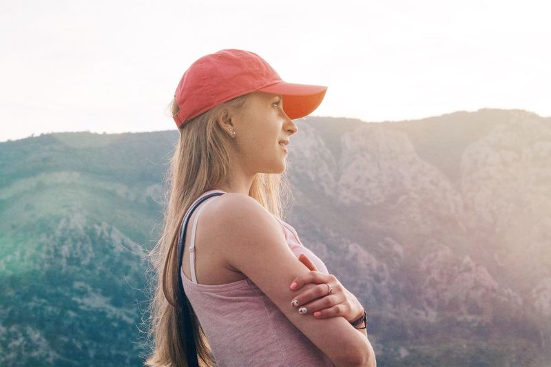 Side View Of Thoughtful Young Woman By Mountain Against Sky