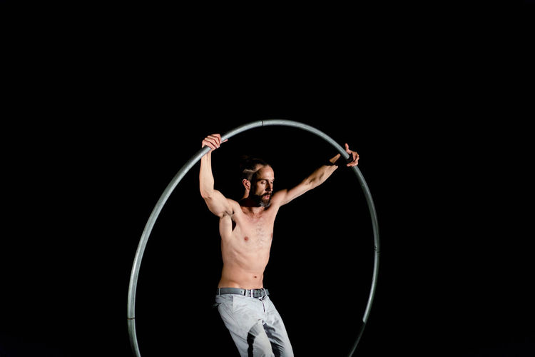 Circus Adult Arms Raised Black Background Casual Clothing Circle Front View Geometric Shape Holding Human Arm Human Body Part Indoors  Limb One Person Performance Plastic Hoop Skill  Standing Studio Shot Three Quarter Length Young Adult