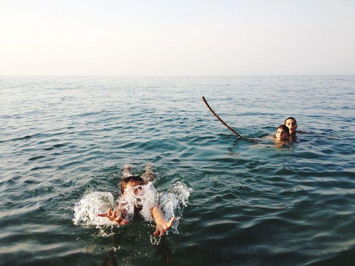Children In Sea Against Clear Sky